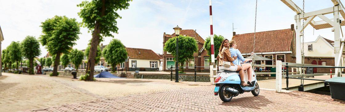Banner voor de Unigarant scooterverzekering met twee dames op een scooter